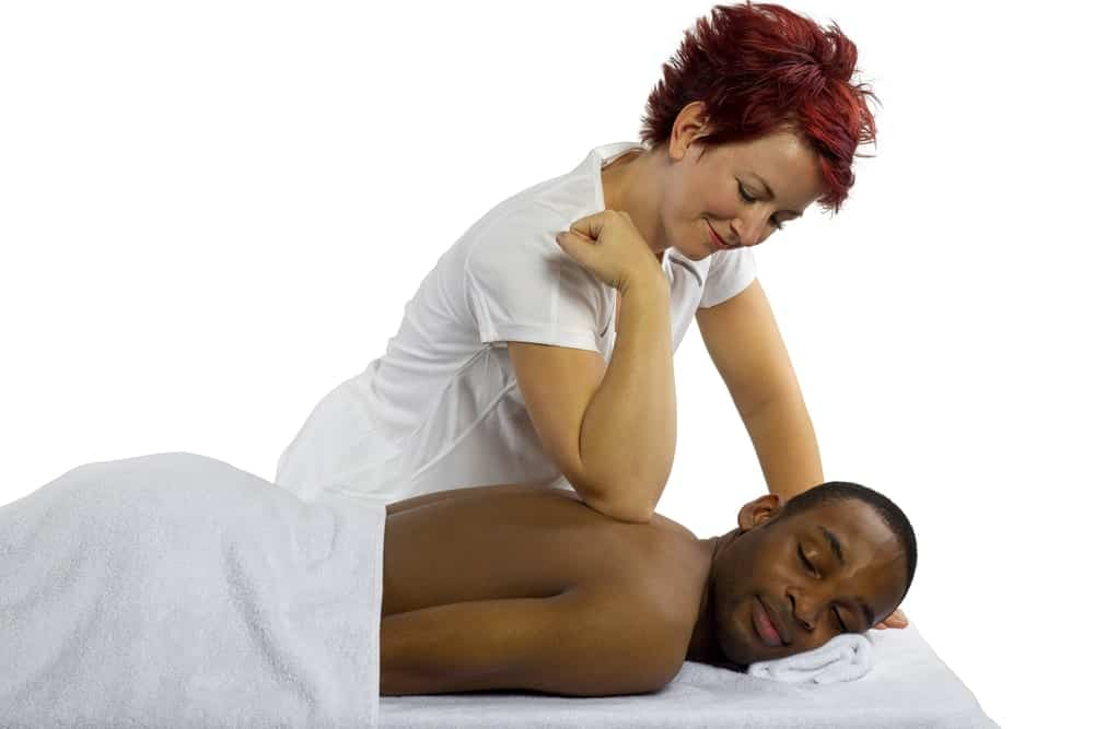 A female masseuse treating a male client with deep tissue massage.