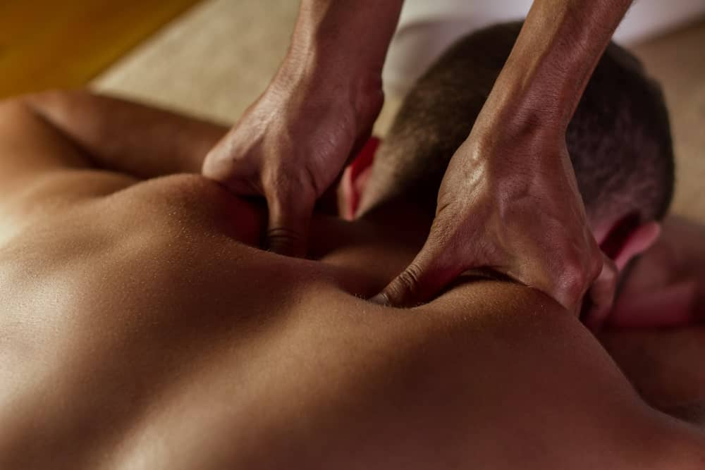 A man having a deep tissue massage on his upper back.