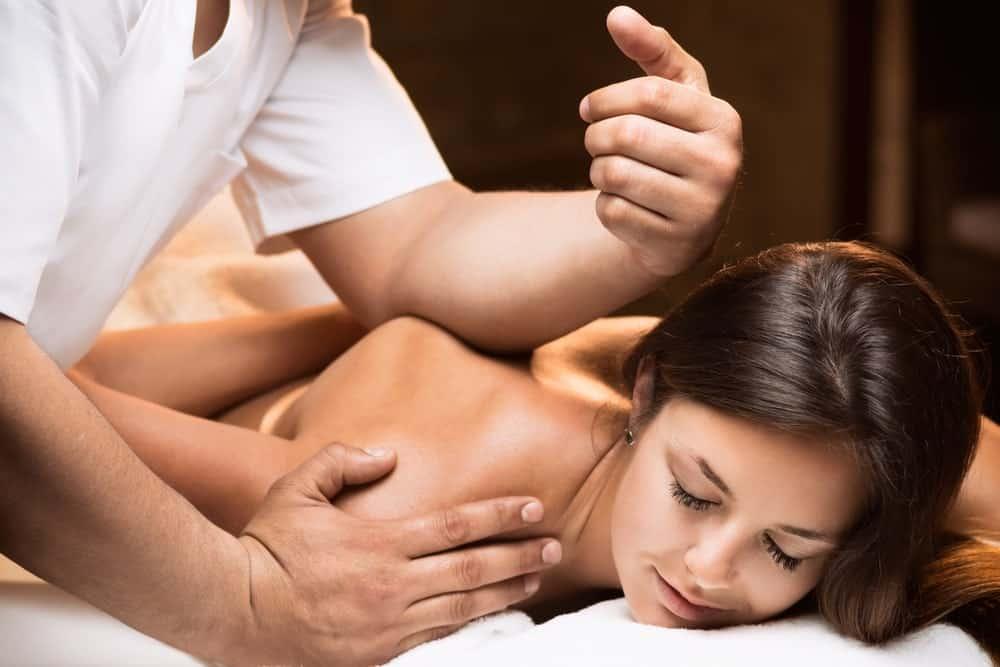 A woman enjoying a deep tissue massage on her back.