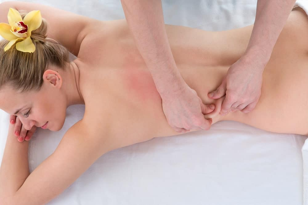 A woman having a deep tissue massage on her lower back.