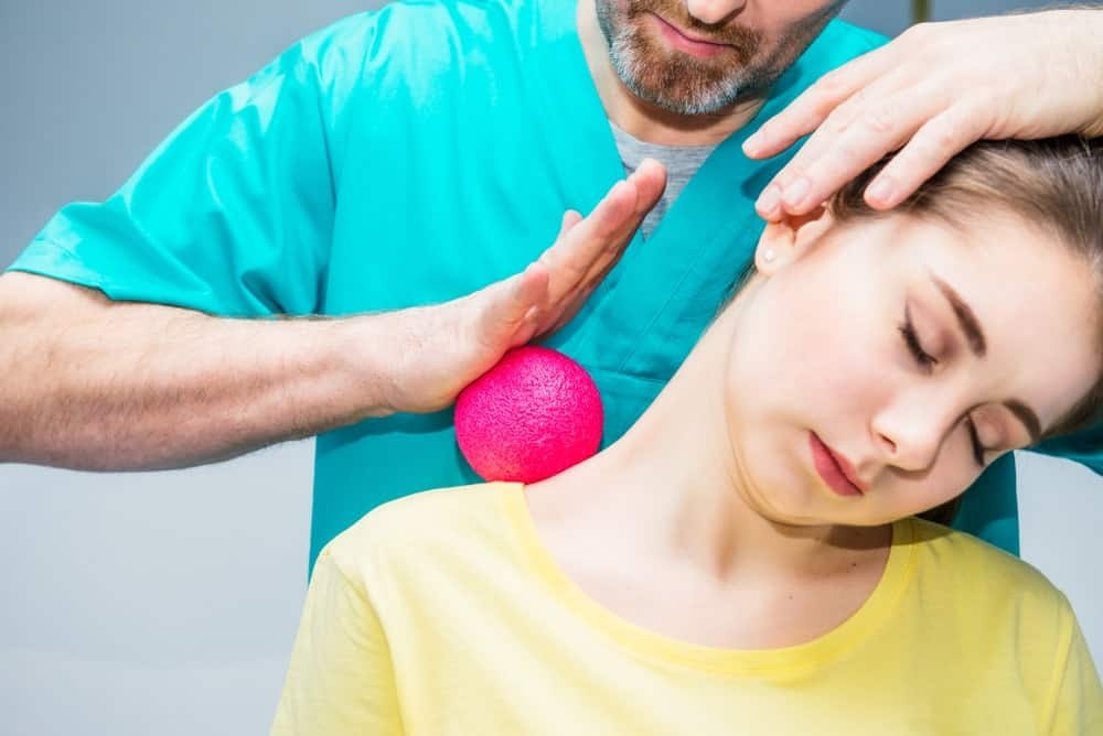 A physical therapist using a massage ball on woman's neck.