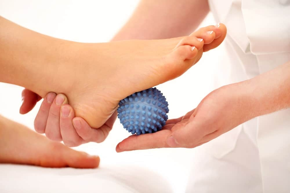 A physical therapist using a massage ball on a patient's foot.