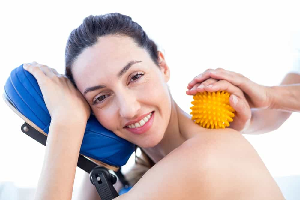 A woman having a neck massage with the use of a massage ball.