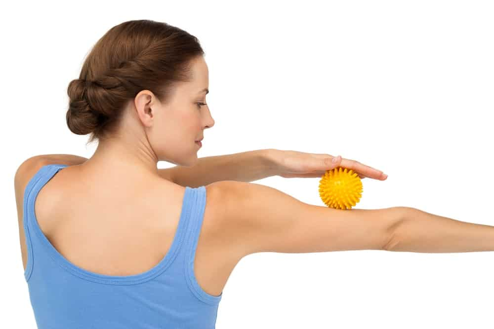 A woman using a massage ball on her arm.
