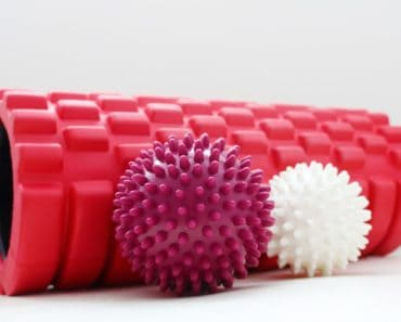 A foam roller and a couple of massage balls on a white surface.