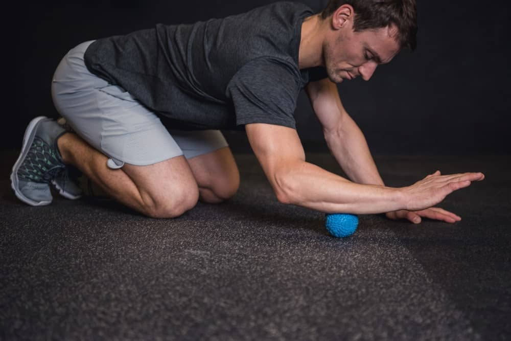 An athletic man using a massage ball on his forearm.