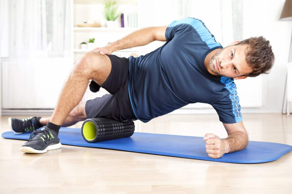 An athletic man exercising with the use of a foam roller.