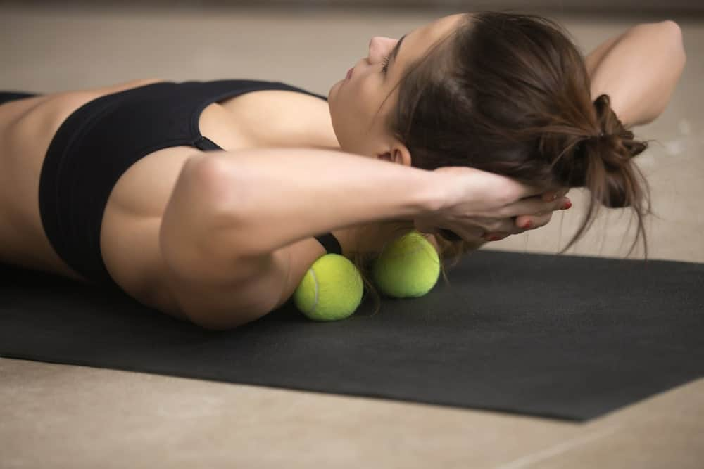 An athletic woman using a couple of tennis balls to massage her back.