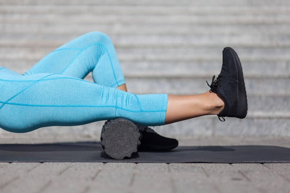 A woman using a black foam roller on her right leg.