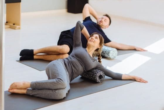 Man and woman doing core exercises while using a foam roller on the floor.