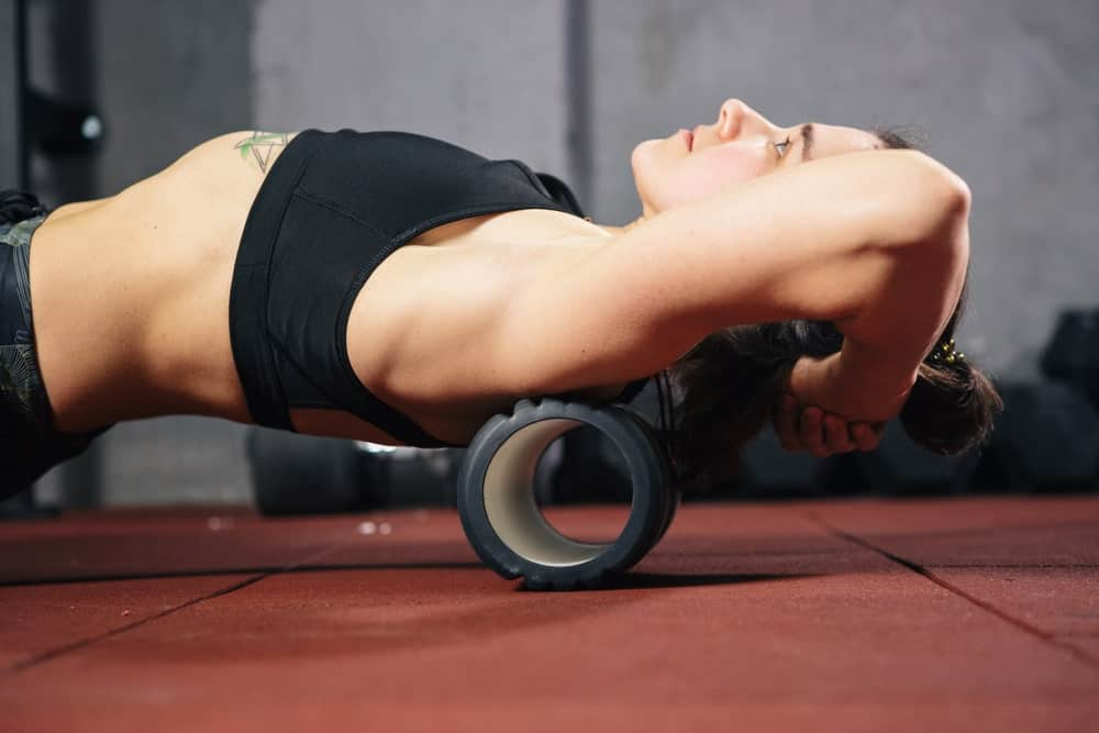 An athletic woman doing an exercise with the use of a foam roller.