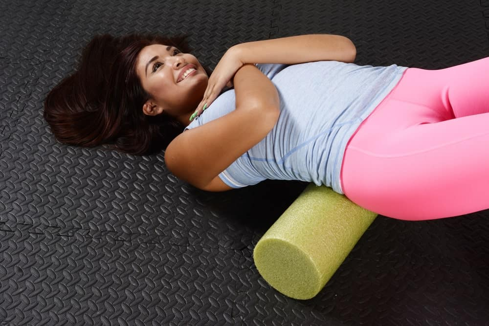 An athletic woman using a foam roller on her lower back.