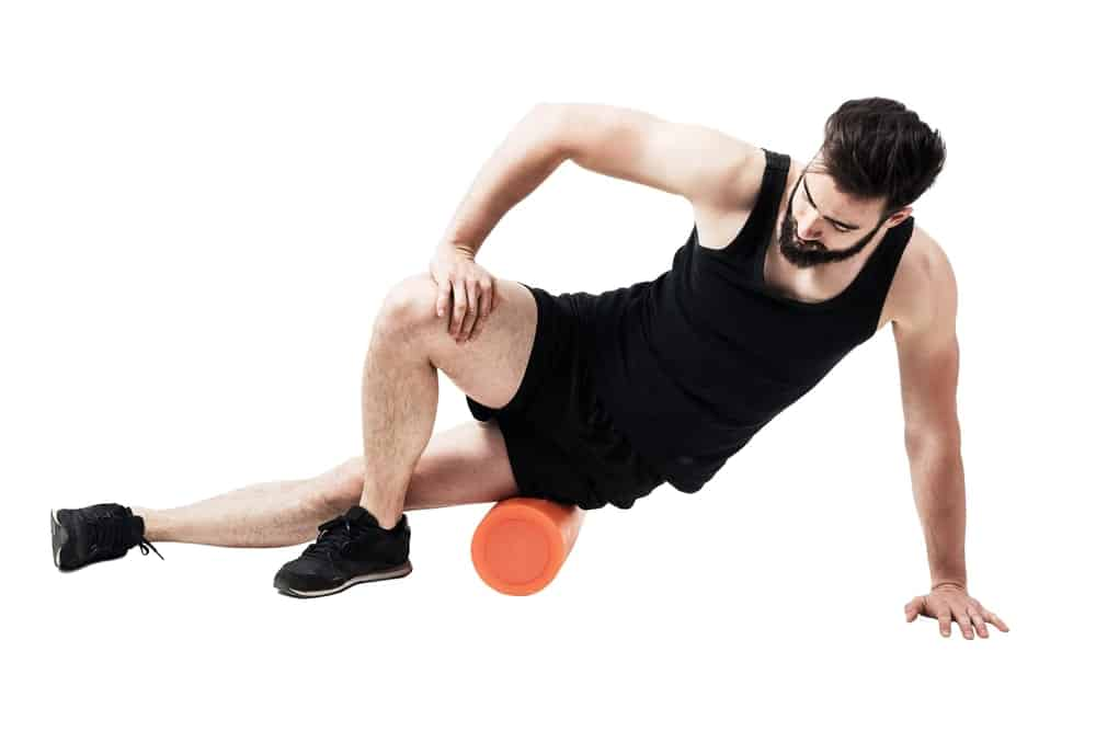 A man doing his stretching with the use of a foam roller.