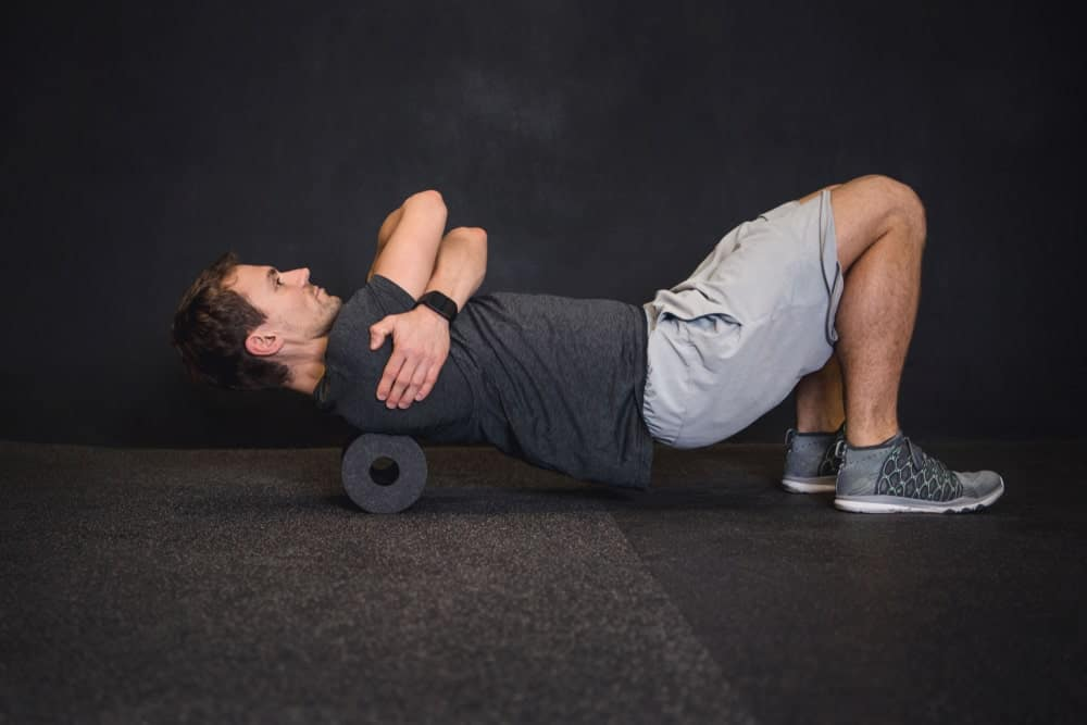 An athletic man doing core exercises on the floor using a black foam roller.