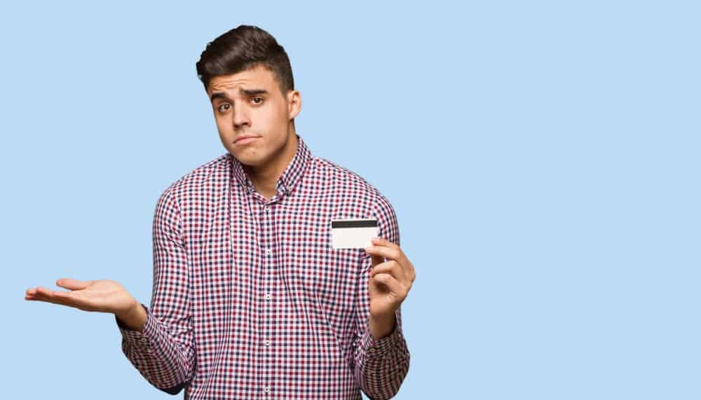 A man in doubt shrugging while holding a credit card.