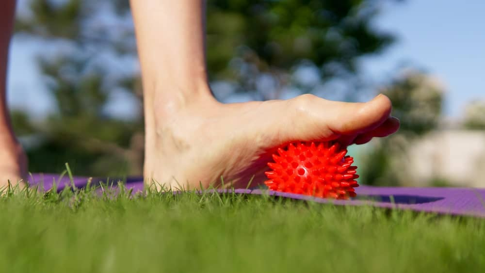 Woman massaging foot using a spiny plastic red massage ball.