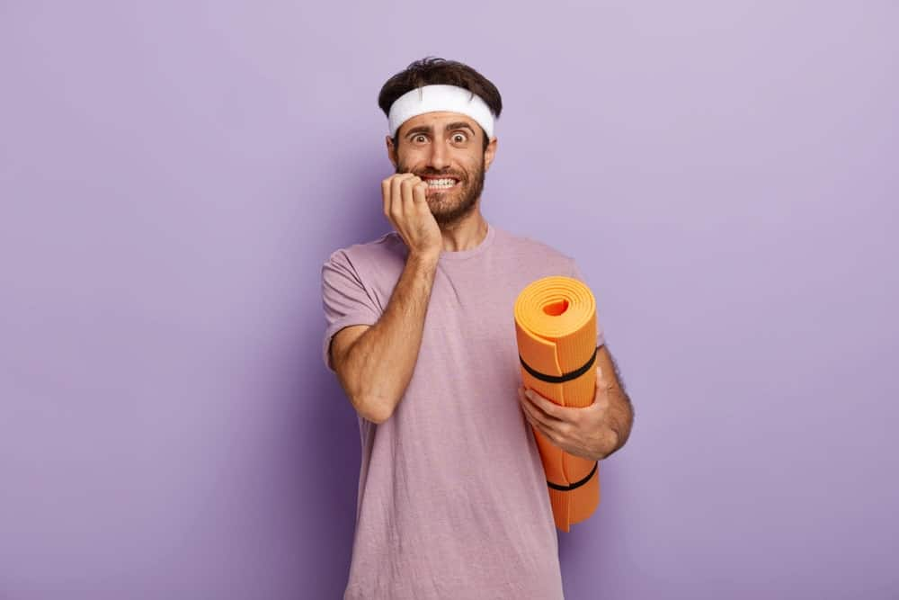 Man in his active wear biting his nails and holding a yoga mat.