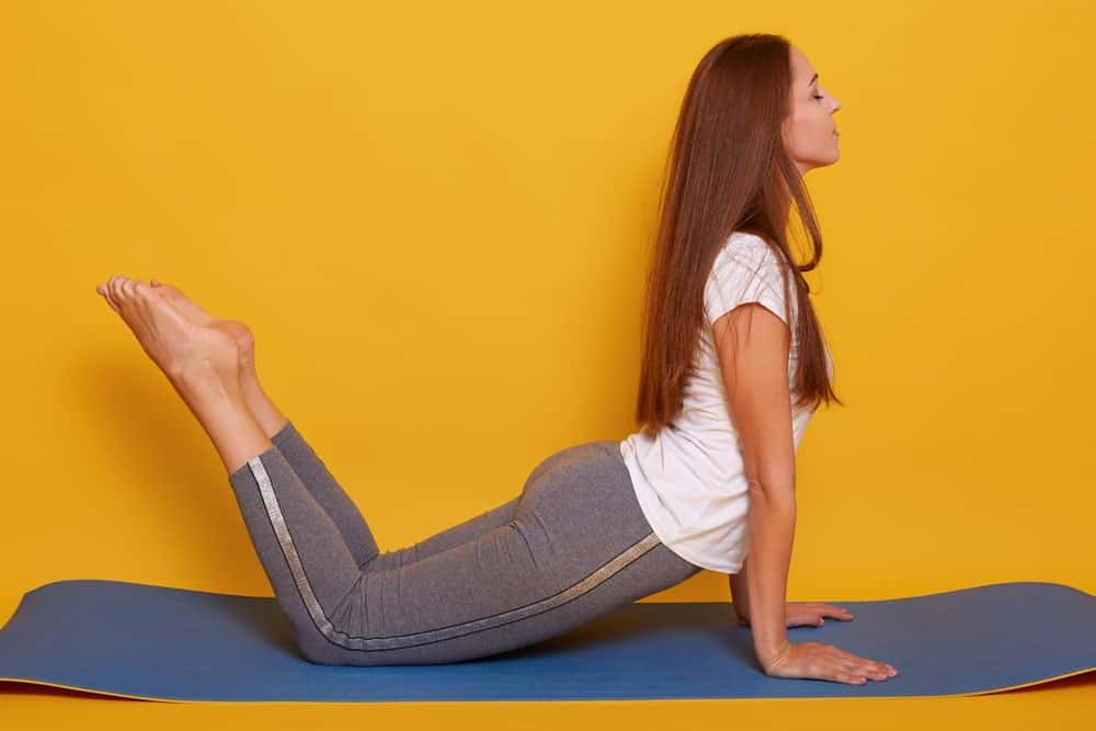Woman doing a cobra yoga pose in her tee shirt.