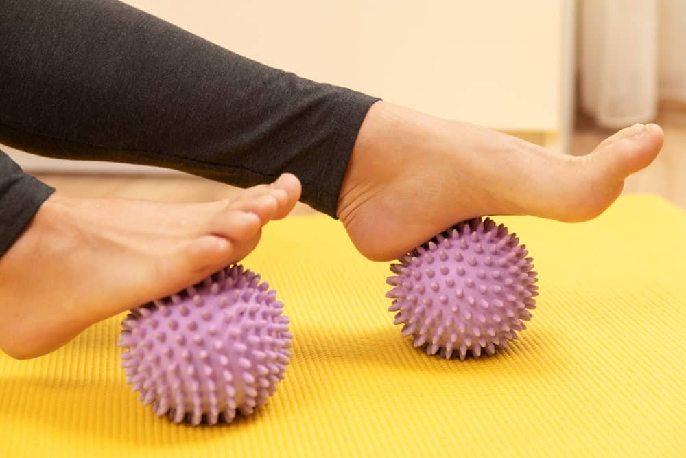 Woman's feet on spiky massage balls.