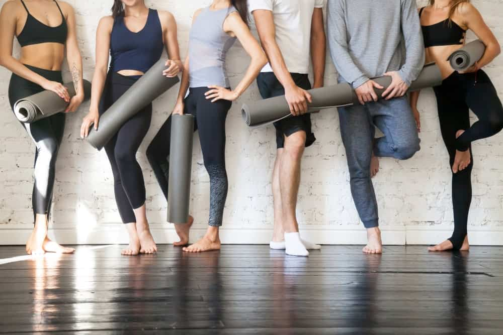 Yogis standing against a white brick wall.