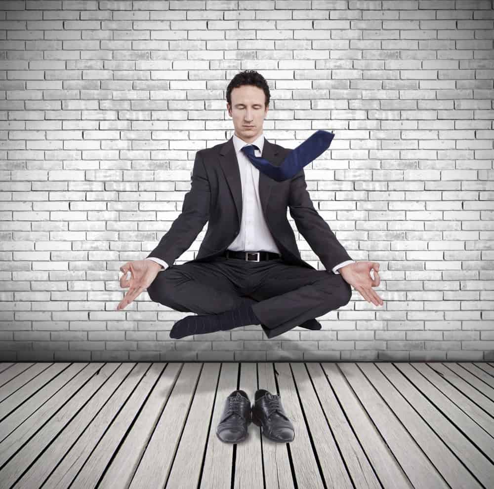 A businessman meditates on a lotus position and floats on air against a backdrop of brick wall and a pair of black shoes on wood flooring.