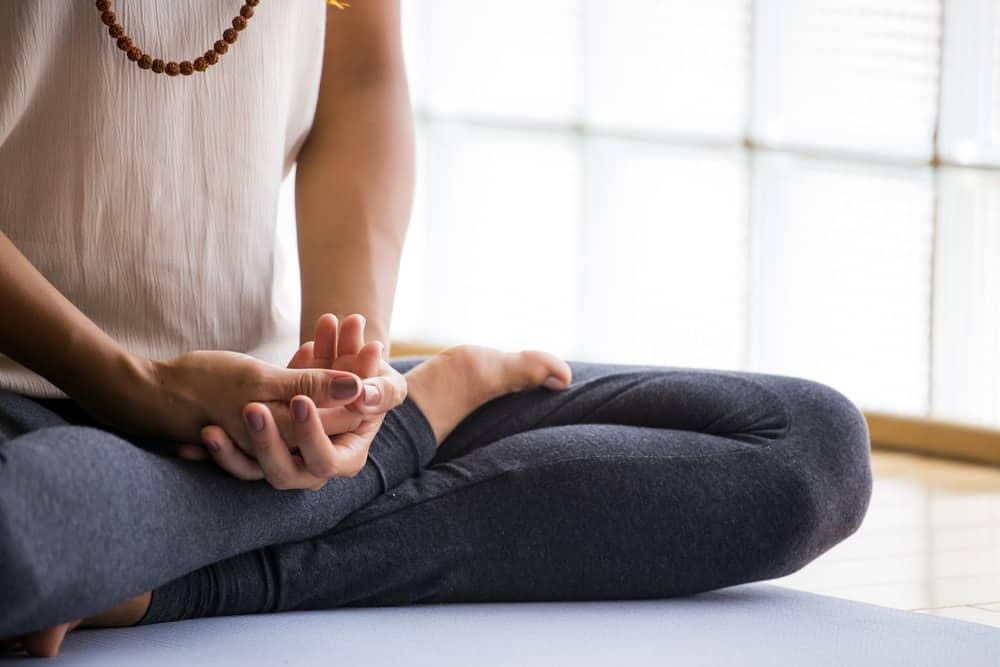 Cropped image of a woman sitting on a lotus position with hands clasped over her legs.