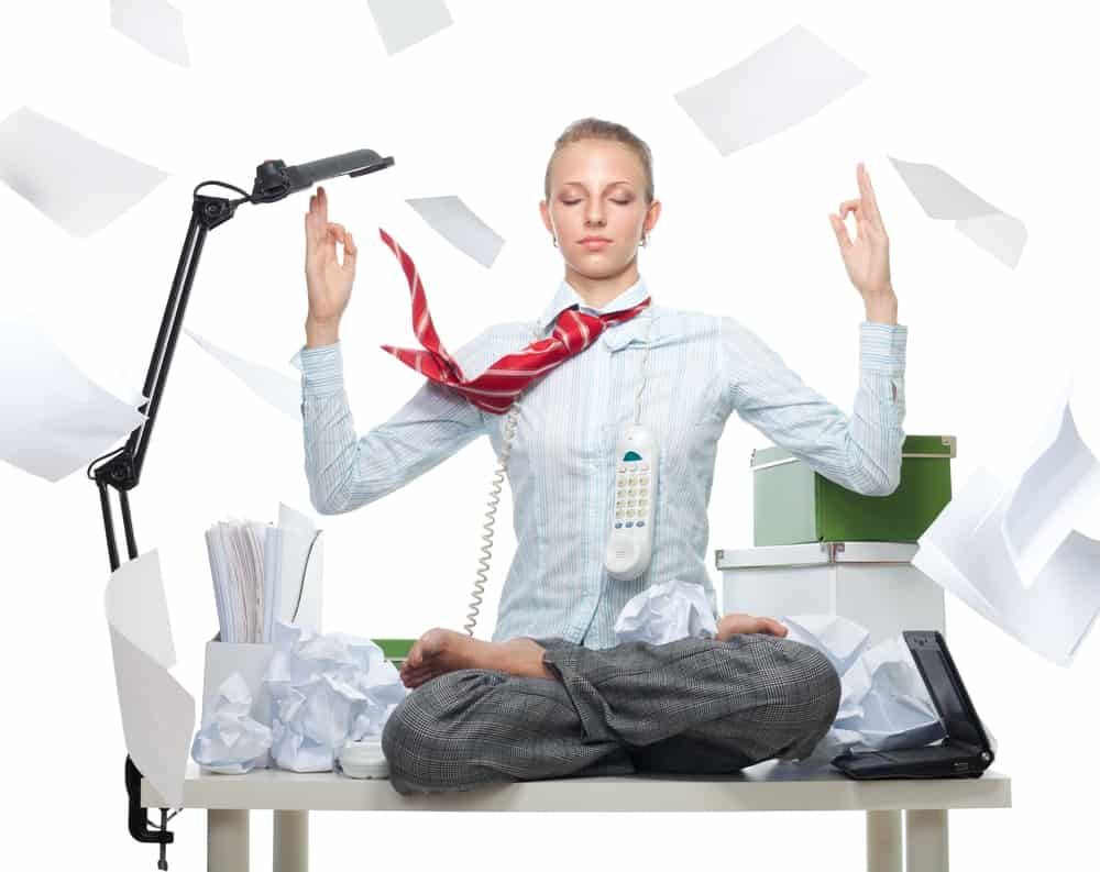 A young woman meditates on a lotus position on top of a messy work desk filled with boxes, crumpled papers, an open laptop, a phone hanging around her neck, and surrounded by papers flying all over her.