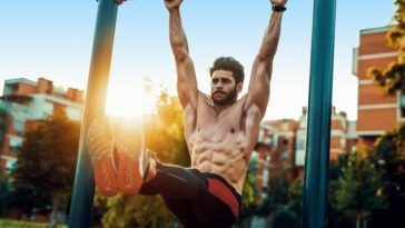 A man doing core exercises on a horizontal bar outdoors.