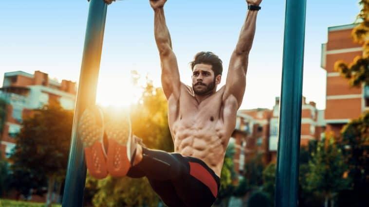 A man doing core exercises on a horizontal bar outdoors.