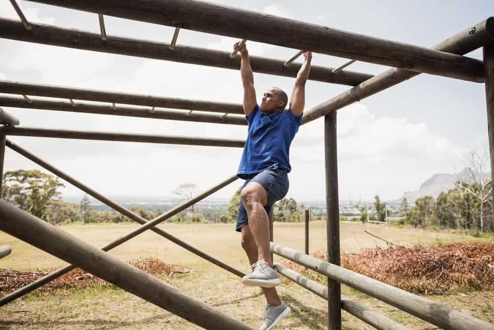 A man climbing through the monkey bars.