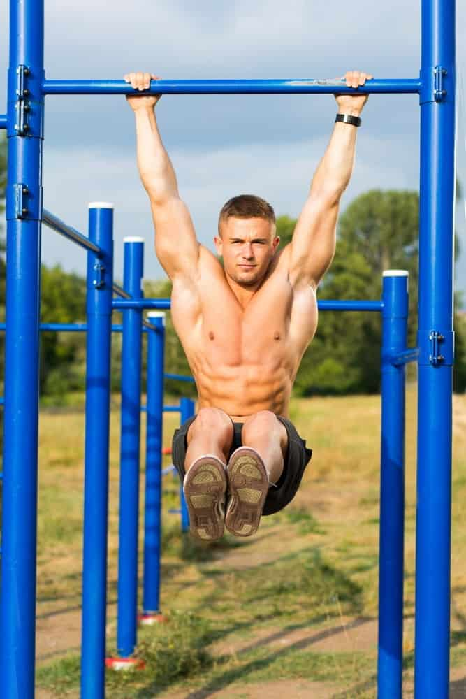 A man doing crunches on the monkey bars.