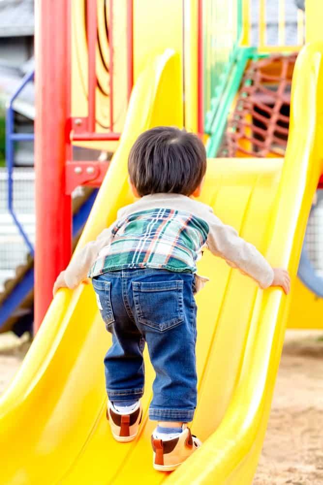 A toddler climbing up the slide.