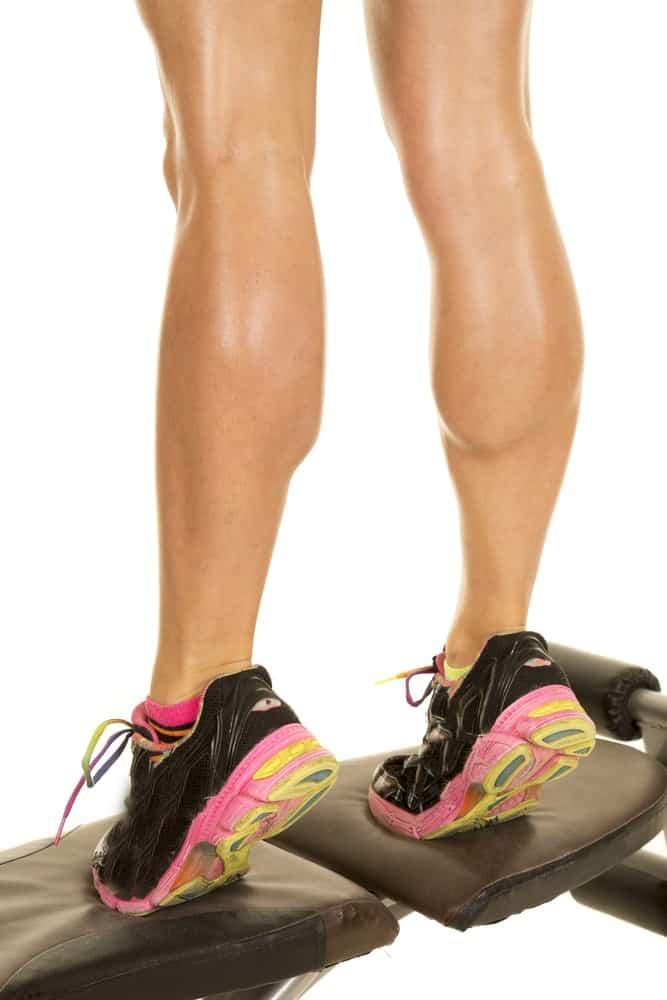 A close look at a woman's legs as she does calf raises.