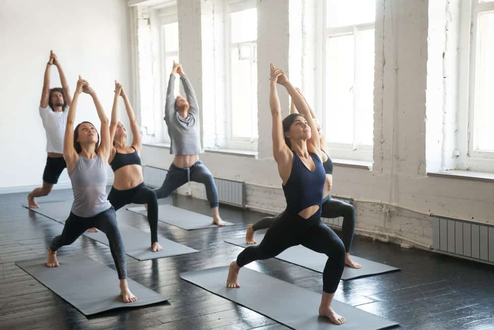 A yoga class doing the warrior one pose.