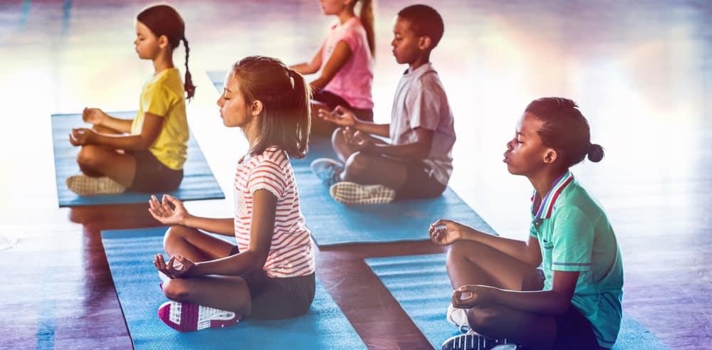 A group of kids meditating.