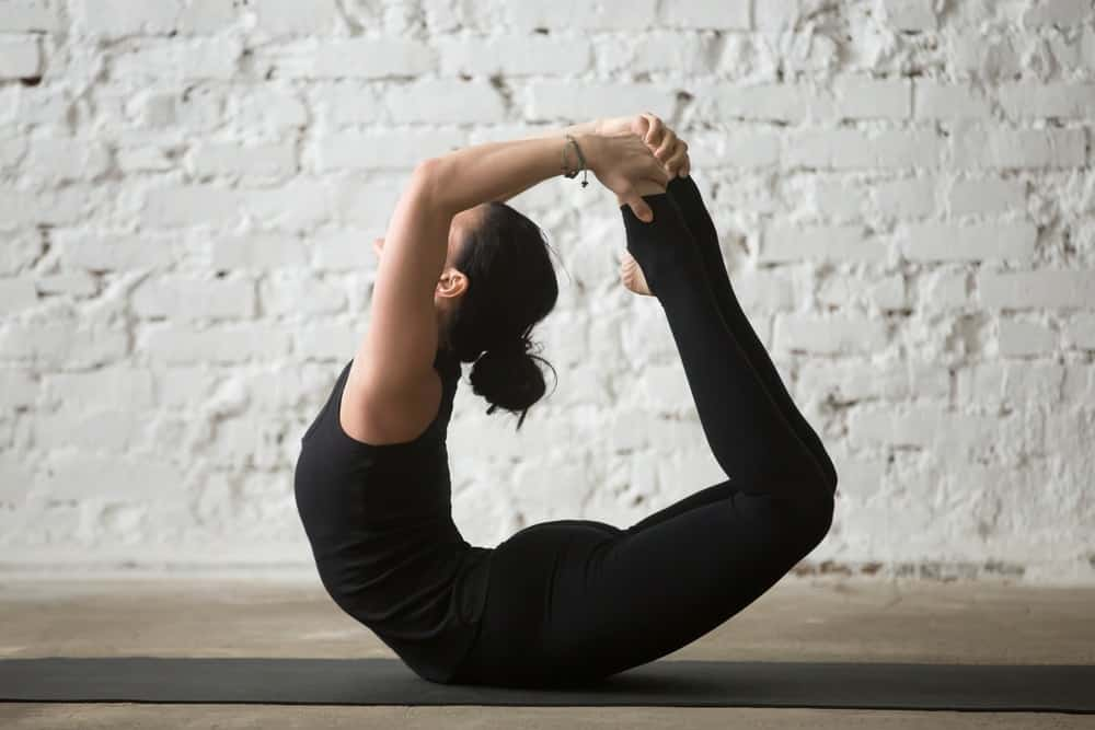 A flexible woman doing the bow pose.
