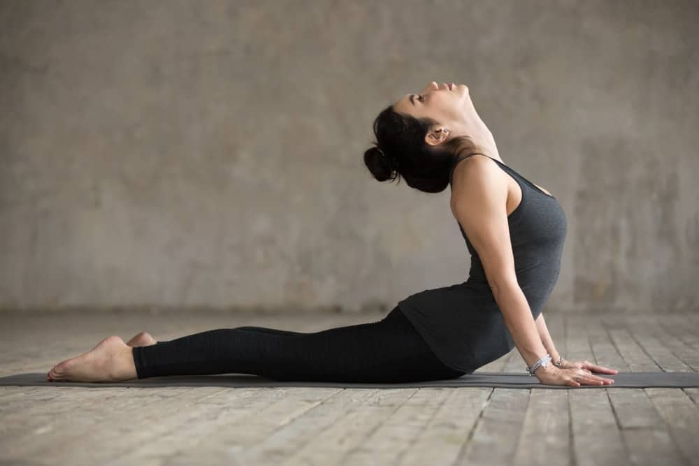 A flexible woman doing the cobra stretch pose.
