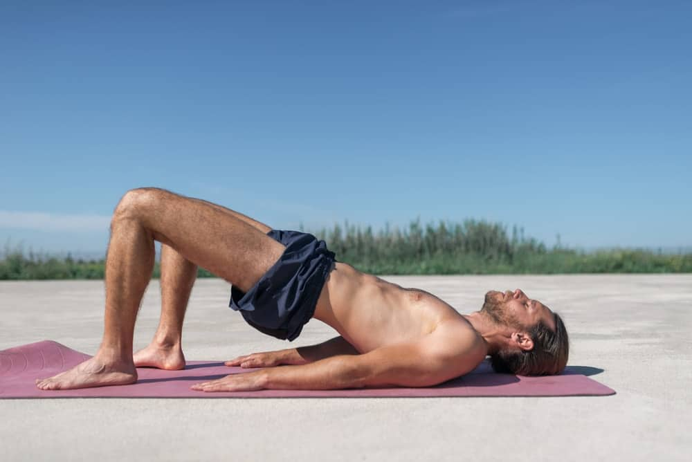 A man doing the pelvic curl on the beach.