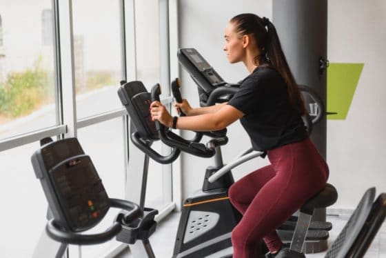 A woman exercising with an indoor cycling machine.