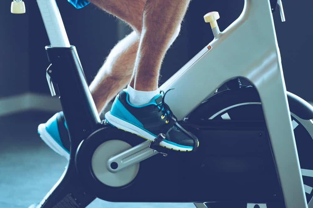 A close look at a man doing indoor cycling at the gym.