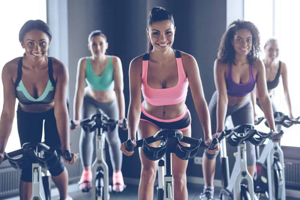 A group of women exercising together with indoor cycling.