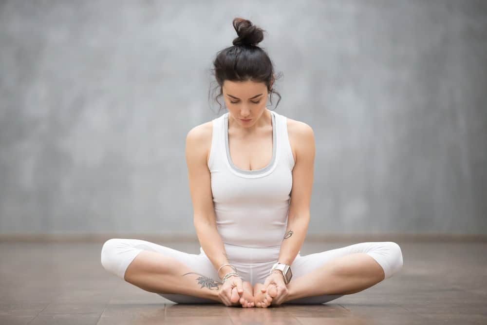 Woman sitting in a butterfly pose.