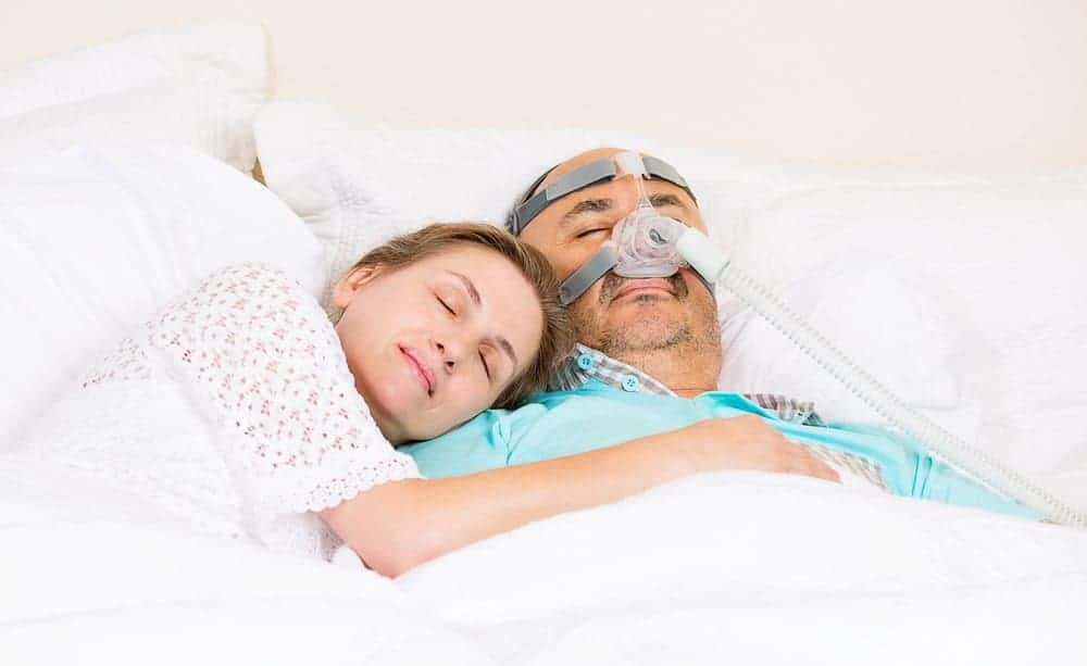 Wife sleeps peacefully while hugging her husband who's wearing a CPAP machine for sleep apnea.