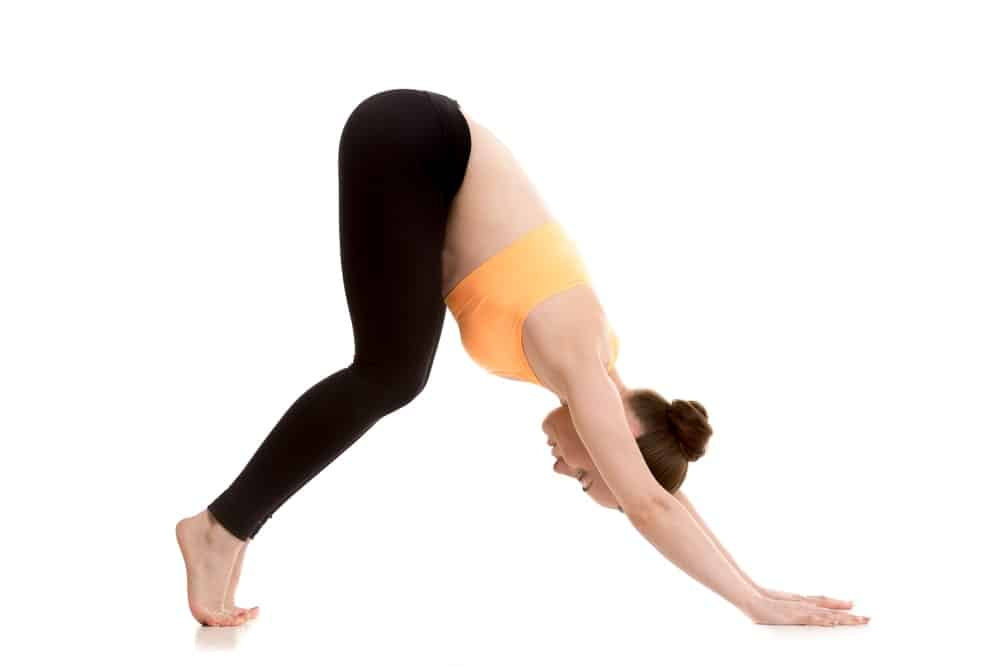 Woman doing an easy variation of downward-facing dog pose.
