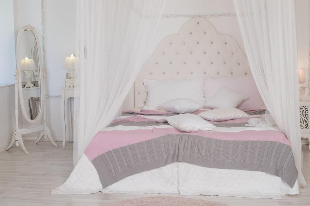 Four poster bed with white canopy drapes, pastel-colored bedding, and an oval mirror on the side..