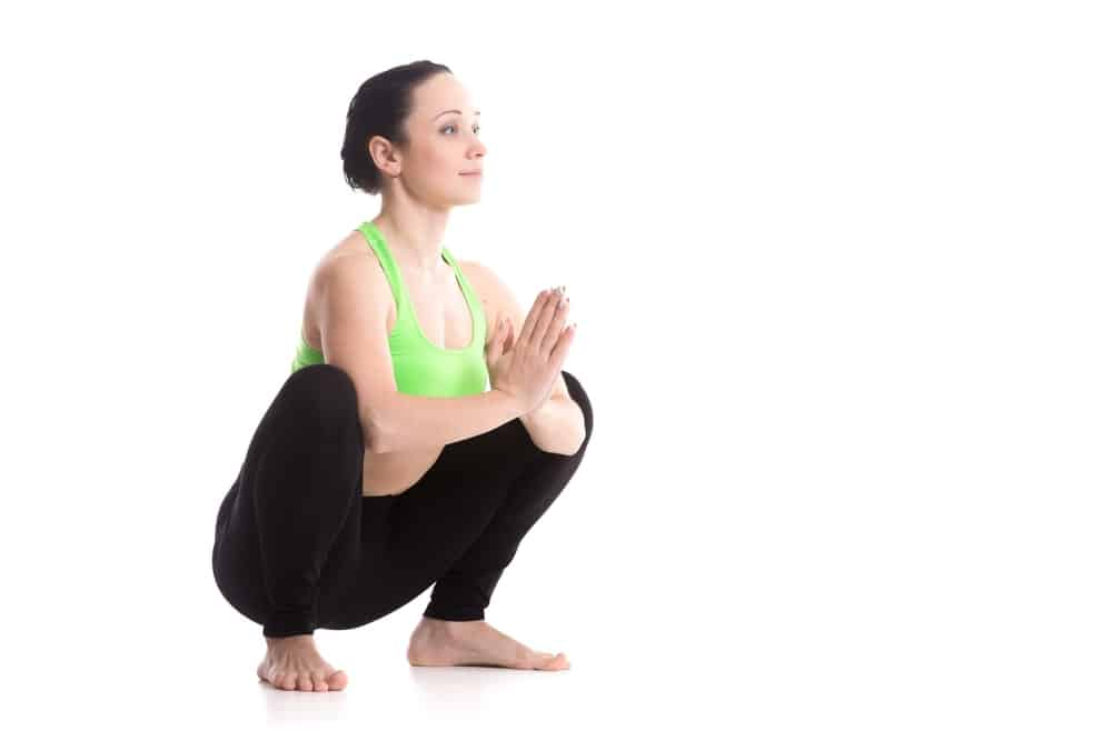 Woman sitting in Garland yoga Pose.