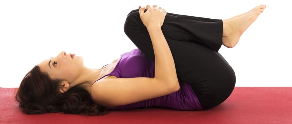 A woman doing the knees to chest yoga pose.