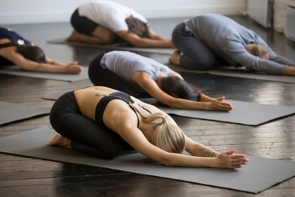 A group of people doing the balasana yoga pose.