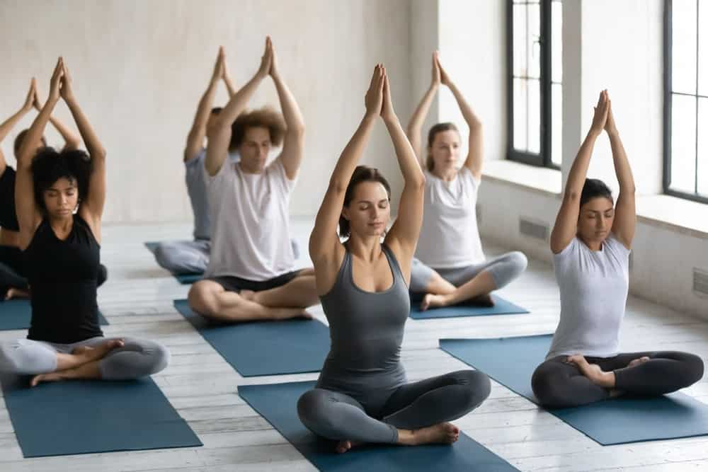 A group of people practicing gentle yoga at a studio.