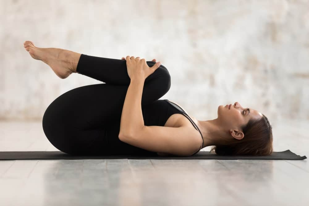 Woman doing chest to knees pose.